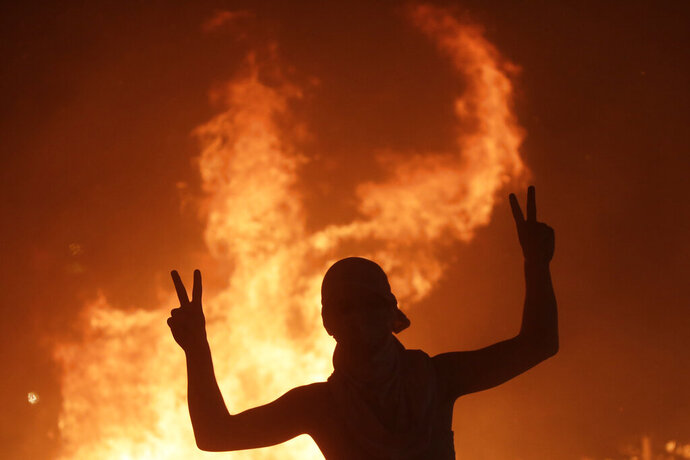 An anti-government protester makes victory signs in front a fire set to block a road during a demonstration in Beirut, Lebanon, Thursday, Oct. 17, 2019. Scores of people are protesting in Beirut and other parts of Lebanon over the government's plans to impose new taxes amid a harsh economic crisis in the country. (AP Photo/Hassan Ammar)
