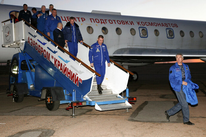 In this photo provided by Roscosmos, Russian cosmonaut Alexey Ovchinin, center, and U.S. astronaut Nick Hague, center left, arrive in Baikonur airport, Kazakhstan, Thursday, Oct. 11, 2018, after an emergency landing following the failure of a Russian booster rocket carrying them to the International Space Station. (Roscosmos via AP)