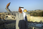 Emirati singer Walid Aljasim, uses his phone overlooking the Dome of the Rock mosque during his visit in Jerusalem, Thursday, Dec. 3, 2020. (AP Photo/Mahmoud Illean)