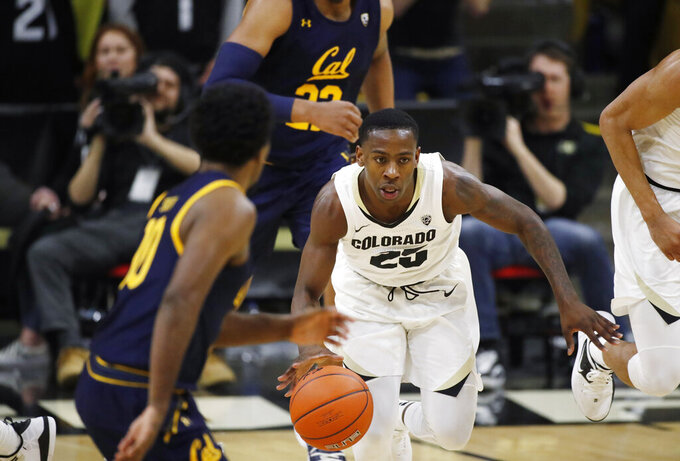 Colorado guard McKinley Wright IV, center, picks up the ball between California guard Matt Bradley, front, and forward Andre Kelly in the second half of an NCAA college basketball game Thursday, Feb. 6, 2020, in Boulder, Colo. (AP Photo/David Zalubowski)