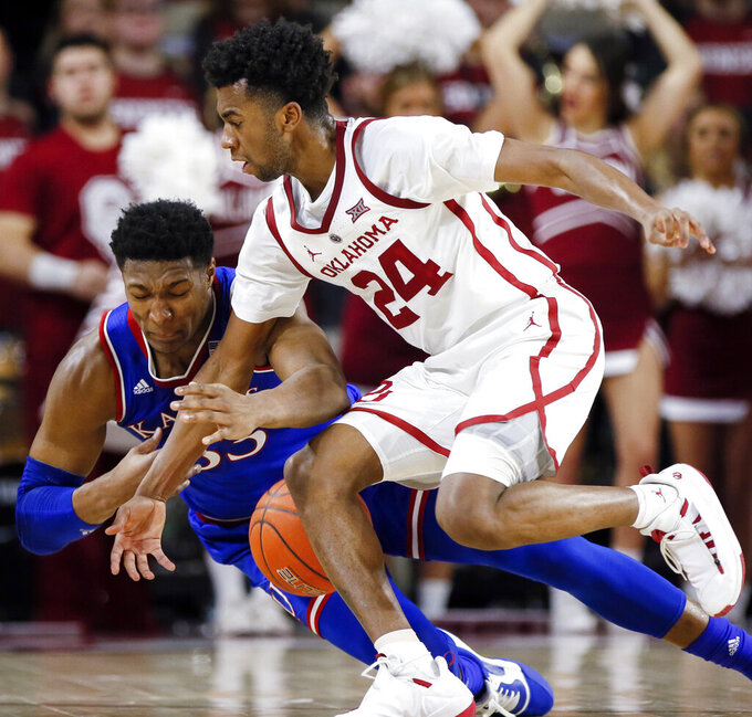 Kansas forward David McCormack (33) and Oklahoma guard Jamal Bieniemy (24) fight for the ball in the first half of an NCAA college basketball game in Norman, Okla., Tuesday, March 5, 2019. (AP Photo/Nate Billings)