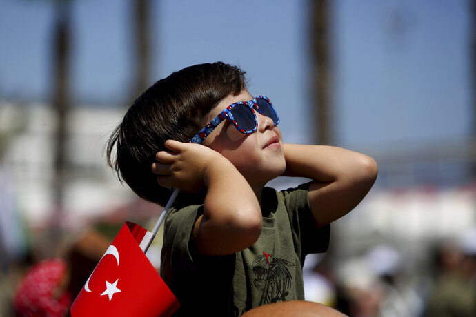 A boy holding a Turkish flag watches as Turkish acrobatic jets fly, during a military parade celebration marking the 45th anniversary of the 1974 Turkish invasion in the Turkish occupied area of the divided capital Nicosia, Cyprus, Saturday, July 20, 2019. Cyprus was split into Greek Cypriot south and Turkish Cypriot north in 1974 when Turkey invaded in response to a coup by supporters of a union with Greece. (AP Photo/Petros Karadjias)