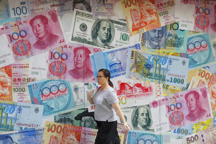FILE - In this Aug. 6, 2019, file photo, a woman walks by a money exchange shop decorated with different countries currency banknotes at Central, a business district in Hong Kong. China's trade with the United States fell sharply in August as a tariff war that threatens global economic growth worsened. (AP Photo/Kin Cheung, File)