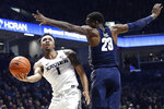 Xavier's Paul Scruggs (1) shoots against Georgetown's Josh LeBlanc (23) during the first half of an NCAA college basketball game, Wednesday, Jan. 9, 2019, in Cincinnati. (AP Photo/John Minchillo)