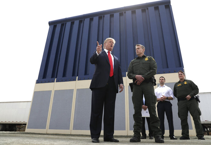 FILE - In this March 13, 2018, file photo, President Donald Trump speaks during as he reviews border wall prototypes, in San Diego, as Rodney Scott, the Border Patrol's San Diego sector chief, listens. The Trump administration has named Rodney Scott the new head of the U.S. Border Patrol. Scott will take over for Carla Provost, who is retiring, according to an announcement obtained Friday by The Associated Press from Mark Morgan, acting head of U.S. Customs and Border Protection. Scott has been a member of the Border Patrol for 27 years. (AP Photo/Evan Vucci, File)