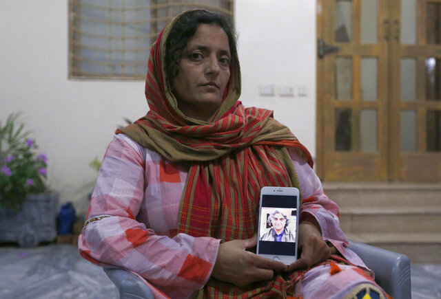 Kaneez Sughra, wife of kidnaped prominent Pakistani journalist Matiullah Jan, shows a picture her husband to journalists at a family's home, in Islamabad, Pakistan, Tuesday, July 21, 2020. Jan, known for his hard hitting criticism of the country's powerful institutions, including its military, is missing, human rights groups and a family member said Tuesday. (AP Photo/Anjum Naveed)