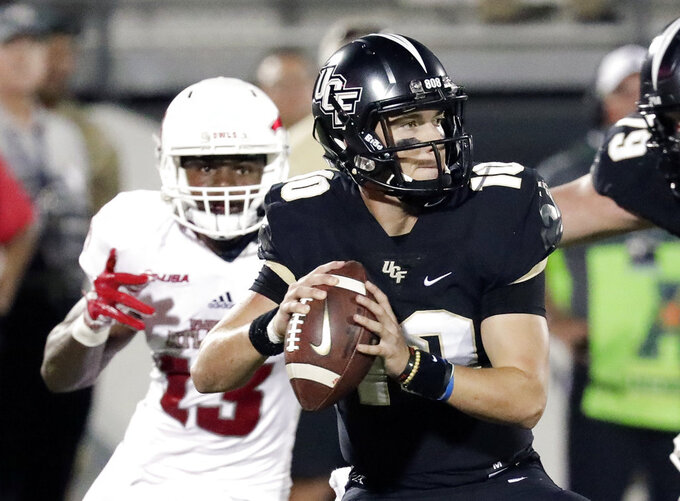 Central Florida quarterback McKenzie Milton, right, looks for a receiver as he is pressured by Florida Atlantic defensive end Leighton McCarthy (13) during the first half of an NCAA college football game, Friday, Sept. 21, 2018, in Orlando, Fla. (AP Photo/John Raoux)