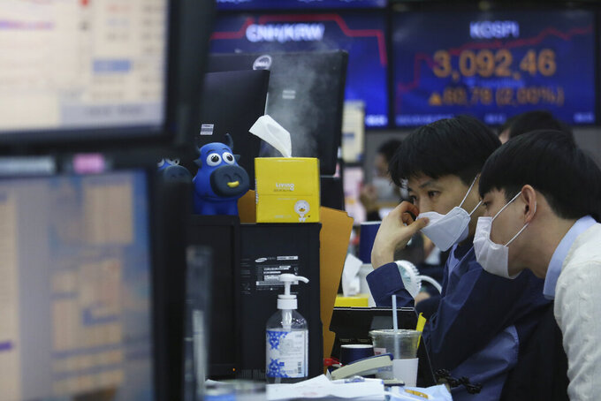 Currency traders watch monitors at the foreign exchange dealing room of the KEB Hana Bank headquarters in Seoul, South Korea, Friday, Jan. 8, 2021. Asian shares mostly rose Friday on hopes for additional economic stimulus after U.S. Congress confirmed Joe Biden as the winner of the presidential election. (AP Photo/Ahn Young-joon)