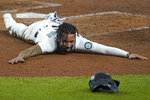 Seattle Mariners shortstop J.P. Crawford sprawls on the dirt and reacts after sliding safely home during the fifth inning of a baseball game against the Houston Astros, Wednesday, Sept. 23, 2020, in Seattle. Crawford scored on a double hit by Kyle Seager. (AP Photo/Ted S. Warren)