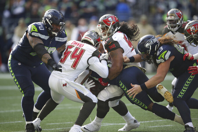 Tampa Bay Buccaneers outside linebacker Lavonte David (54) and defensive tackle Vita Vea, center, wrap up Seattle Seahawks running back Chris Carson (center, obscured) as Seahawks' Mike Iupati, left, and Joey Hunt, right, look on during the first half of an NFL football game, Sunday, Nov. 3, 2019, in Seattle. (AP Photo/Scott Eklund)