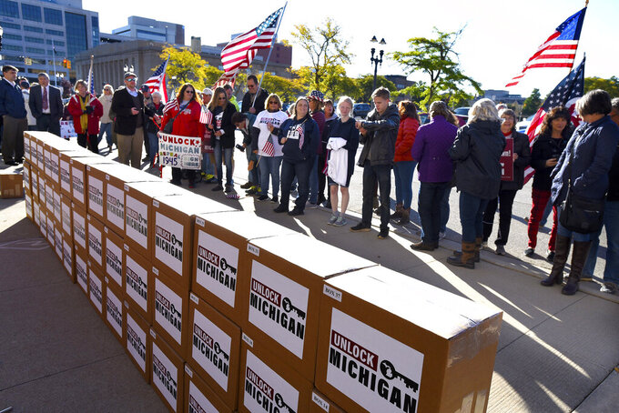 FILE - In this Oct. 2, 2020 file photo, a group gathers as boxes filled with petition signatures are delivered by Unlock Michigan to the Michigan Department of State Bureau of Elections in Lansing, Mich. The Michigan Supreme Court on Friday, June 11, 2021, unanimously ordered the state elections board to certify a veto-proof initiative that would let Republican legislators wipe from the books a law Gov. Gretchen Whitmer used to issue sweeping pandemic orders. (Rod Sanford/Detroit News via AP, File)