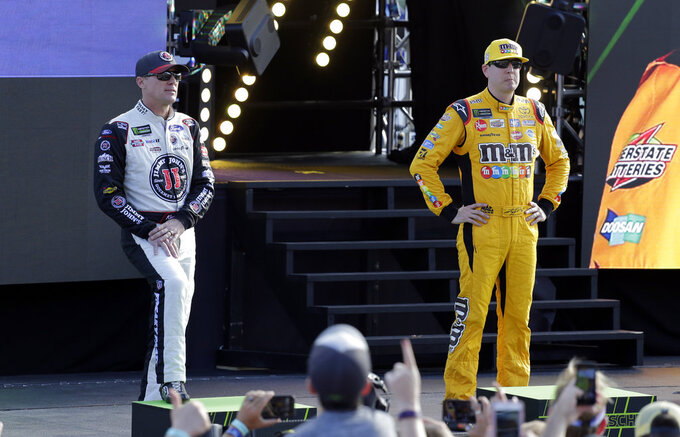 Kevin Harvick, left, and Kyle Busch, right, are introduced before a NASCAR Cup Series Championship auto race at the Homestead-Miami Speedway, Sunday, Nov. 18, 2018, in Homestead, Fla. (AP Photo/Terry Renna)
