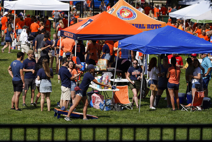 Illinois football fans tailgate before an NCAA college football game between Illinois and Nebraska on Saturday, Aug. 28, 2021, in Champaign, Ill. Colleges across the country are cautiously optimistic that pregame tailgating will largely return to normal even since the emergence of the delta variant of the coronavirus. (AP Photo/Charles Rex Arbogast)