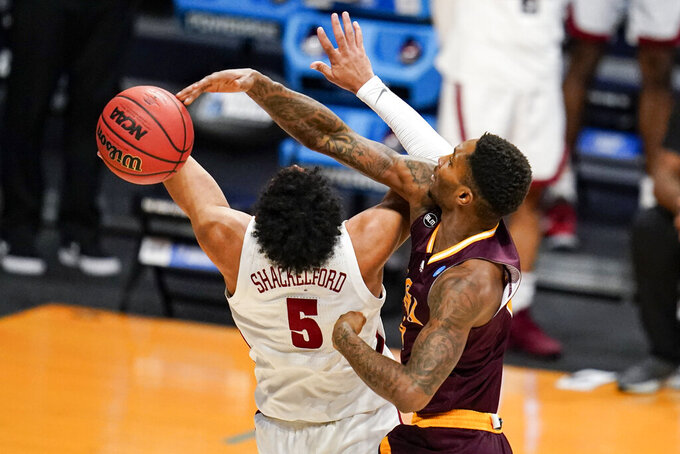 Iona guard Berrick JeanLouis (0) blocks the shot of Alabama guard Jaden Shackelford (5) in the second half of a first-round game in the NCAA men's college basketball tournament at Hinkle Fieldhouse in Indianapolis, Saturday, March 20, 2021. (AP Photo/Michael Conroy)