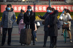 People wearing face masks to protect against the spread of the coronavirus wait to cross an intersection in Beijing, Wednesday, Jan. 20, 2021. China is now dealing with coronavirus outbreaks across its frigid northeast, prompting additional lockdowns and travel bans. (AP Photo/Mark Schiefelbein)