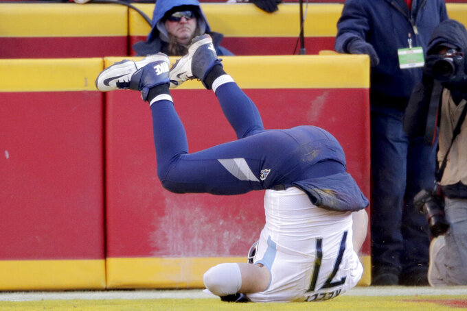 Tennessee Titans' Dennis Kelly flips over as he catches a touchdown pass during the first half of the NFL AFC Championship football game against the Kansas City Chiefs Sunday, Jan. 19, 2020, in Kansas City, MO. (AP Photo/Charlie Riedel)