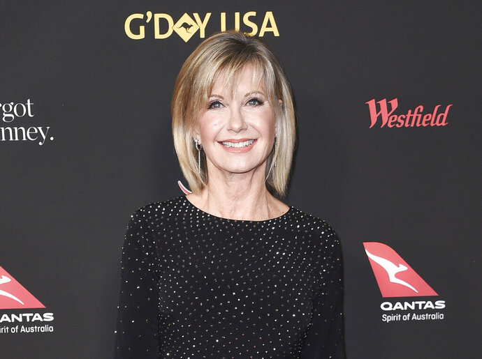 """FILE - In this Jan. 27, 2018 file photo, Olivia Newton-John attends the 2018 G'Day USA Los Angeles Gala at the InterContinental Hotel Los Angeles. Two collectors said you're the one that I want to Newton-John's iconic """"Grease"""" leather jacket and skintight pants at an auction in Beverly Hills, Saturday, Nov. 2, 2019. Julien's Auctions says the combined ensemble, which Newton-John's character Sandy wears in the closing number of the 1978 film, fetched $405,700 total. The leather jacket sold for $243,200 and the pants, which Newton-John famously had to be sewn into, went for $162,500.   (Photo by Richard Shotwell/Invision/AP, File)"""
