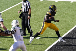 Iowa running back Tyler Goodson (15) scores on a 9-yard touchdown run during the first half of an NCAA college football game against Michigan State, Saturday, Nov. 7, 2020, in Iowa City, Iowa. (AP Photo/Charlie Neibergall)