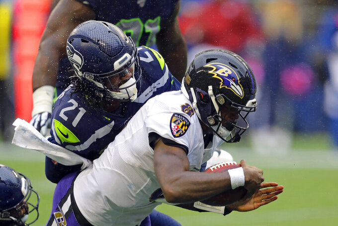 Baltimore Ravens quarterback Lamar Jackson (8) is hit by Seattle Seahawks cornerback Tre Flowers (21) while scoring a touchdown on a fourth-down keeper play during the second half of an NFL football game, Sunday, Oct. 20, 2019, in Seattle. (AP Photo/John Froschauer)