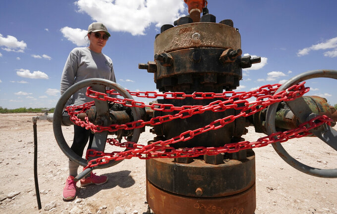 Ashley Williams Watt looks at an abandoned well wrapped with locks and chains on her ranch, Friday, July 9, 2021, near Crane, Texas. Some of her wells are leaking chemicals such as benzene, a known carcinogen, into fields and drinking water. (AP Photo/Eric Gay)