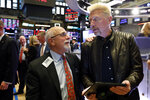 Trader Peter Tuchman, left, meets tennis great Boris Becker during his visit to the trading floor of the New York Stock Exchange, Friday, Aug. 23, 2019. Stocks tumbled on Wall Street after President Donald Trump said he