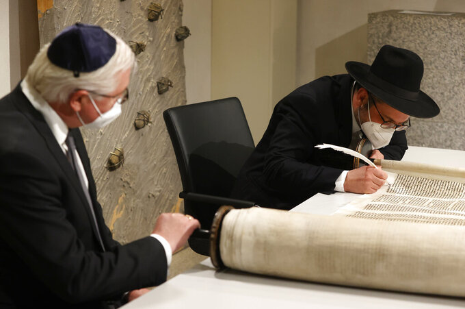 German President Frank-Walter Steinmeier, right, and Rabbi Shaul Nekrich, right, take part in a ceremony at the Reichstag building in Berlin, Germany, Wednesday, Jan. 27, 2021 to complete the historic Sulzbach Torah Scroll from 1792, rediscovered in 2013 and just restored. The ceremony takes place on the International Holocaust Remembrance Day. (Odd Andersen/Pool Photo via AP)