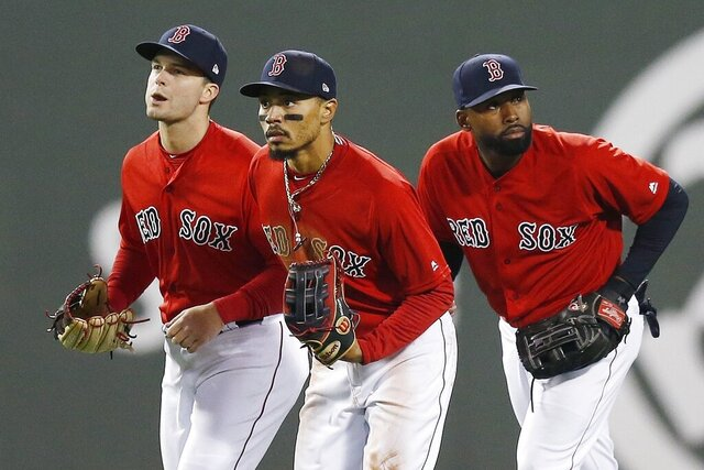 FILE - In this Friday, April, 12, 2019 file photo, Boston Red Sox's Andrew Benintendi, left, Mookie Betts, center, and Jackie Bradley Jr. run in after defeating the Baltimore Orioles during a baseball game in Boston. When the Boston Red Sox traded Mookie Betts to the Los Angeles Dodgers on the eve of spring training, they broke up the