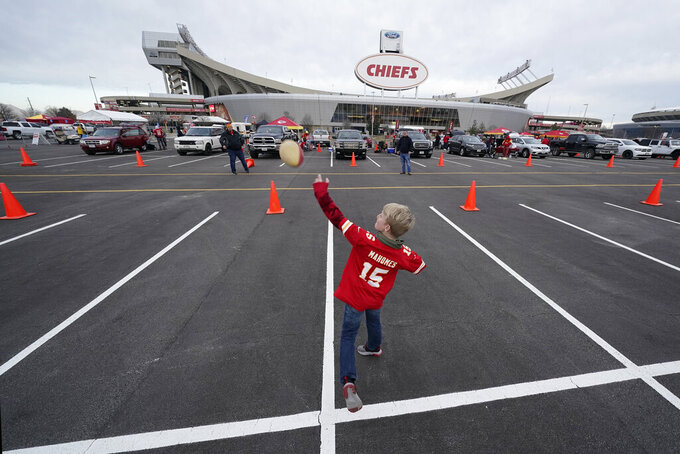 Nine-year-old Hudson Henry plays catch while tailgating in the parking lot at Arrowhead stadium before an NFL football game between the Atlanta Falcons and the Kansas City Chiefs Sunday, Dec. 27, 2020, in Kansas City, Mo. (AP Photo/Charlie Riedel)