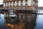 A street vendor pushes his mobile stall through a street flooded by the Negro River, in downtown Manaus, Amazonas state, Brazil, Tuesday, June 1, 2021. Rivers around Brazil's biggest city in the Amazon rain forest have swelled to levels unseen in over a century of record-keeping, according to data published Tuesday by Manaus' port authorities. (AP Photo/Edmar Barros)