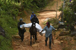 A police officer helps a peasant transport the body of one of at least five people killed during a skirmish between illegal armed groups in Jamundi, southwest Colombia, Friday, Jan. 17, 2020. Authorities say rebels with the former Revolutionary Armed Forces of Colombia operate in the area and may have been involved. (AP Photo/Christian EscobarMora)