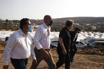 European Council President Charles Michel, center, is accompanied by Greek officials visits the new temporary refugee camp in Kara Tepe on the northeastern island of Lesbos, Greece, Tuesday, Sept. 15, 2020. Greece has called on the European Union to jointly run new refugee camps being built on its eastern islands as part of a planned overhaul of the bloc's migration policy. (Dimitris Tosidis/Pool via AP)