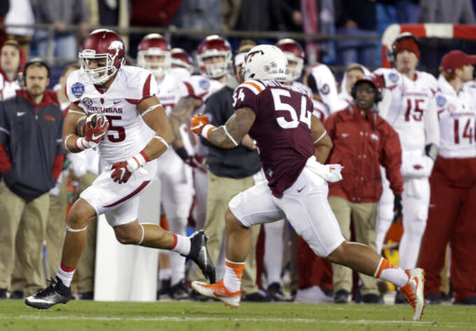 FILE - In this Dec. 29, 2016, file photo, Arkansas's Cheyenne O'Grady, left, runs down the sideline as he is pursued by Virginia Tech's Andrew Motuapuaka, right, during the first half of the Belk Bowl NCAA college football game in Charlotte, N.C. O'Grady missed Arkansas' first two games of the season while suspended, and he saw little action in the next two. The junior tight end has emerged as one of the Razorbacks top offensive options in the last two games, however, including a two-touchdown effort against No. 1 Alabama last week. (AP Photo/Bob Leverone, File)