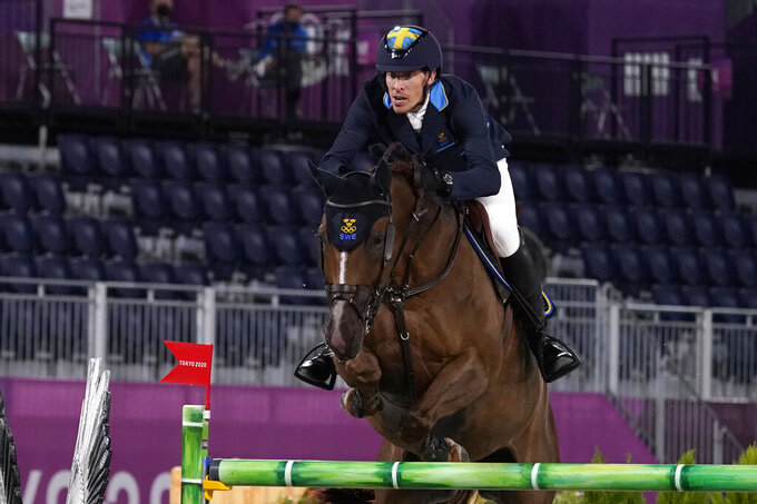 Sweden's Henrik von Eckermann, riding King Edward, competes in a jump-off during the equestrian jumping team final at Equestrian Park in Tokyo at the 2020 Summer Olympics, Saturday, Aug. 7, 2021, in Tokyo, Japan. (AP Photo/Carolyn Kaster)
