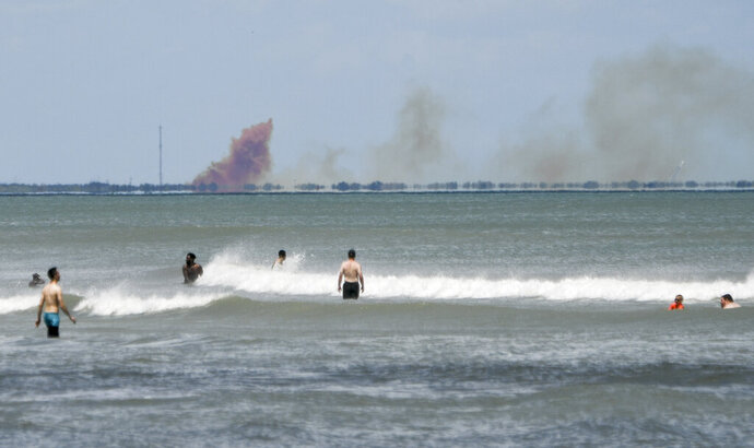 FILE - In this April 20, 2019, file photo, cloud of orange smoke rises over nearby Cape Canaveral Air Force Station, as seen from Cocoa Beach, Fla., after the SpaceX Dragon 2 capsule was destroyed during a test. SpaceX says a leaky valve caused its crew capsule to explode during the test back in April. The company announced the preliminary results of its accident investigation Monday, July 15, 2019. (Craig Bailey/Florida Today via AP, File)