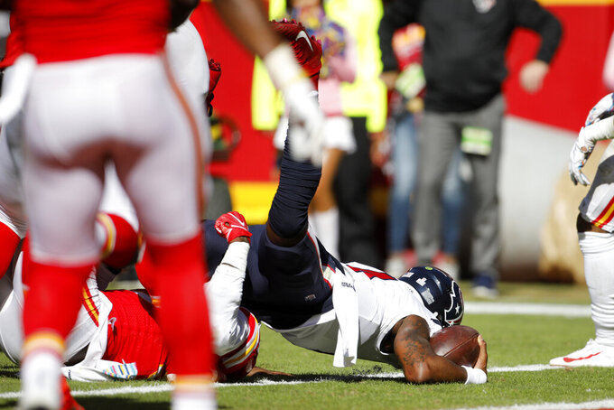 Houston Texans quarterback Deshaun Watson, right, scores a touchdown against Kansas City Chiefs defensive end Frank Clark during the second half of an NFL football game in Kansas City, Mo., Sunday, Oct. 13, 2019. (AP Photo/Colin E. Braley)