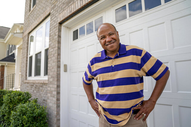 Banking executive Bob Marshall, an active stock investor, poses for a photo at his home in Ashburn, Va., Friday, Aug. 7, 2020. Nearly half of all U.S. households don't own any stocks, and a disproportionate number of them are from Black and other racial-minority households. Differences in financial-literacy education may be one factor, Marshall said. Or, because fewer Black families have wealth that has carried through generations, they may be more wary of risky investments. (AP Photo/J. Scott Applewhite)