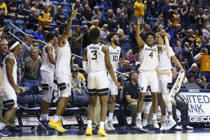 West Virginia players celebrate after a score against Texas during the second half of an NCAA college basketball game Monday, Jan. 20, 2020, in Morgantown, W.Va. (AP Photo/Kathleen Batten)
