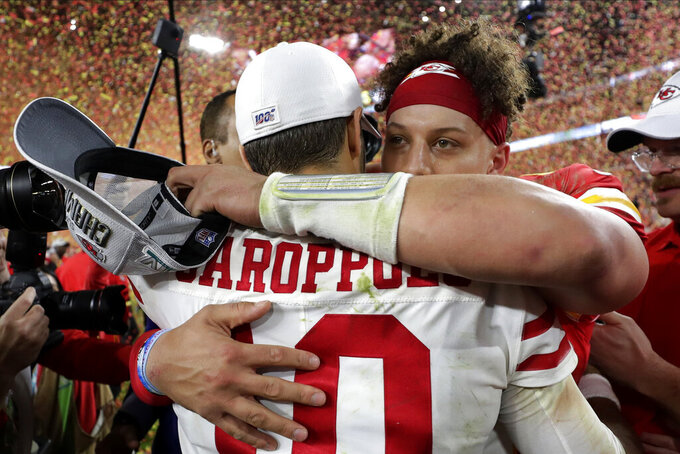 Kansas City Chiefs' quarterback Patrick Mahomes, rear, embraces San Francisco 49ers' quarterback Jimmy Garoppolo after winning the NFL Super Bowl 54 football game Sunday, Feb. 2, 2020, in Miami Gardens, Fla. (AP Photo/Matt York)