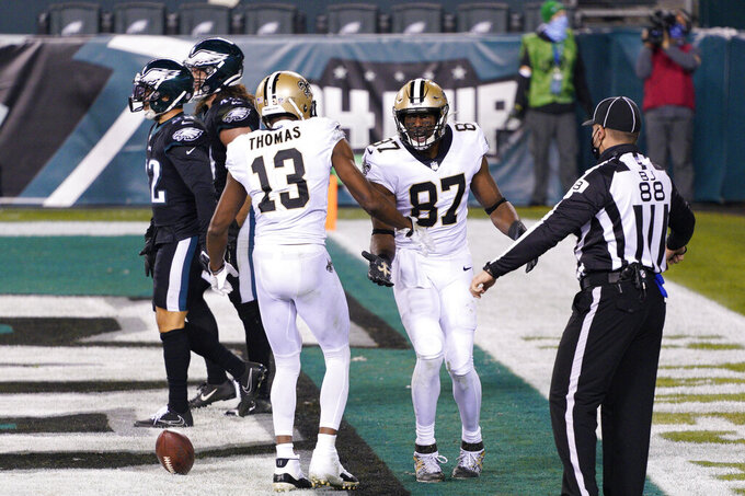 New Orleans Saints' Jared Cook (87) and Michael Thomas (13) celebrate after a touchdown by Cook during the second half of an NFL football game against the Philadelphia Eagles, Sunday, Dec. 13, 2020, in Philadelphia. (AP Photo/Chris Szagola)