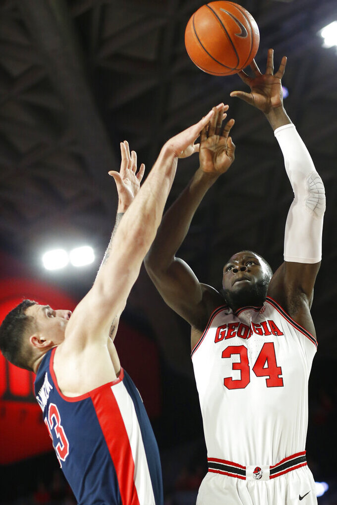 Georgia forward Derek Ogbeide (34) takes a shot over Mississippi center Dominik Olejniczak (13) during an NCAA college basketball game in Athens, Ga., on Saturday, Feb. 9, 2019. (Joshua L. Jones/Athens Banner-Herald via AP)