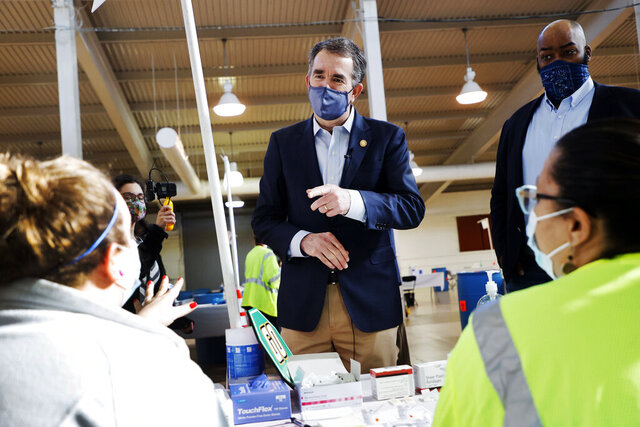 Virginia Gov. Ralph Northam talks with two volunteers who were administering the COVID-19 vaccination at the Richmond Raceway complex in Richmond, Va., Thursday, Jan. 21, 2021. At right is Del. Lamont Bagby, D-Henrico. (Dean Hoffmeyer/Richmond Times-Dispatch via AP)