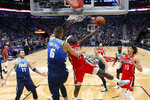 New Orleans Pelicans guard Jrue Holiday (11) goes to the basket against Dallas Mavericks forward Kristaps Porzingis (6) in the first half of an NBA basketball game in New Orleans, Tuesday, Dec. 3, 2019. (AP Photo/Gerald Herbert)