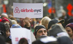 FILE - In this Jan. 20, 2015, file photo, supporters of Airbnb hold a rally outside City Hall in New York. Airbnb faces tightening regulations in New York City that could take a big bite out of its profits, and on Wednesday, Aug. 15, 2018, the short-term rental company offered a counter-measure designed to appease hostile politicians: a $10 million contribution to charities. (AP Photo/Bebeto Matthews, File)