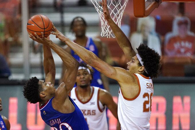 Texas forward Jericho Sims blocks a shot by Kansas guard Ochai Agbaji, left, during the second half of an NCAA college basketball game, Tuesday, Feb. 23, 2021, in Austin, Texas. (AP Photo/Eric Gay)
