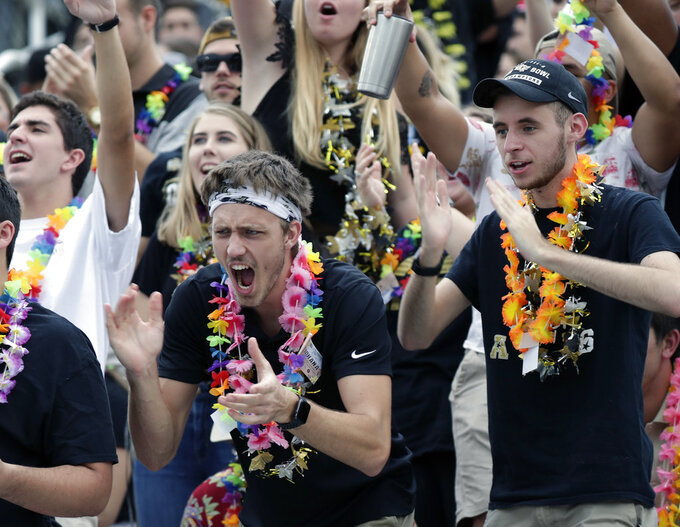 Central Florida students wearing Hawaiian leis cheer before start of the American Athletic Conference championship NCAA college football game between Central Florida and Memphis, Saturday, Dec. 1, 2018, in Orlando, Fla. Over 40,000 leis were distributed to fans before the game to show support for injured quarterback McKenzie Milton who is from Hawaii. (AP Photo/John Raoux)