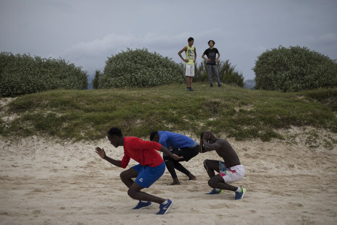 A group of friends exercise together at a beach in Marseille, southern France, Saturday, May 16, 2020. Beaches in Marseille have become partially accessible since the lifting of lockdown measures meant to prevent the spread of coronavirus. (AP Photo/Daniel Cole)