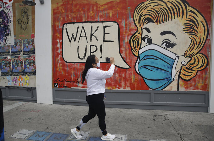"""FILE - In this May 18, 2020, file photo, Mary Cruz takes a cell phone video of a coronavirus-themed mural Monday in the arts district of Los Angeles. Coronavirus cases have surged to record levels in the Los Angeles area, putting the nation's largest county in """"an alarming and dangerous phase"""" that if not reversed could overwhelm intensive care units and usher in more sweeping closures, health officials said Wednesday, July 15. Los Angeles County, home to a quarter of the state's population, reported 2,758 more confirmed cases on Wednesday and 44 deaths. The county's overall death total is just under 4,000. (AP Photo/Marcio Jose Sanchez)"""