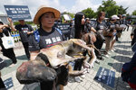 Members of the Last Chance for Animals hold models of slaughtered dogs during a rally to oppose eating dog meat in front of the National Assembly in Seoul, South Korea, Friday, July 12, 2019. July 12 is the day South Koreans eat healthy foods such as dog meat in the belief it would help them survive heat during summer. (AP Photo/Ahn Young-joon)