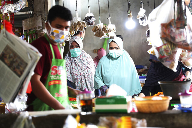 People wear masks at a traditional market in Jakarta, Indonesia, Friday, April 10, 2020. Authorities began stricter measures to halt the new coronavirus' spread in Indonesia's capital Friday, with its normally congested streets empty after death toll spiked in the past week. (AP Photo/Achmad Ibrahim)