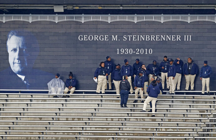Yankee Stadium employees stand beneath a protected overhang by a sign honoring Yankees owner George Steinbrenner after a baseball game between the New York Yankees and the Baltimore Orioles was postponed due to a forecast of inclement weather, Tuesday, May 14, 2019, in New York. This follows Monday night's postponement of a game between the two games which was postponed because of unplayable field conditions due to rainwater in the outfield. Tuesday's game will be played as part of a day-night doubleheader, Aug. 12th. (AP Photo/Kathy Willens)